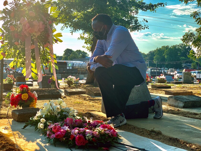 Will Boyd kneels at the grave of a family member who died after contracting the coronavirus, Saturday, June 20, 2020, in Montgomery, Ala. He says his family has lost multiple family members to COVID-19. (AP Photo/Kim Chandler)