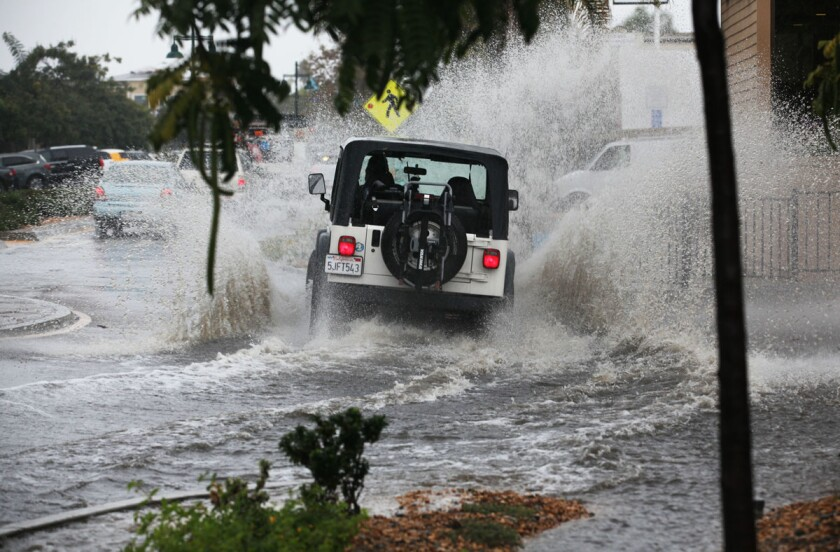 A jeep plows through a deep pocket of water at a traffic circle in Bird Rock Monday morning.