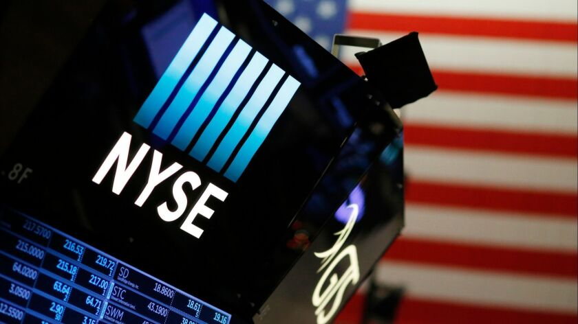 FILE - In this Dec. 27, 2017, file photo, a logo for the New York Stock Exchange is displayed above