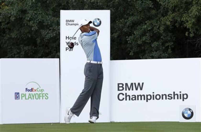 Golfer Tiger Woods watches his tee shot on the ninth hole during the pro-am round of the 2013 BMW Championship golf tournament at Conway Farms Golf Club in Lake Forest. Ill., Wednesday, Sept. 11, 2013. (AP Photo/Charles Rex Arbogast)