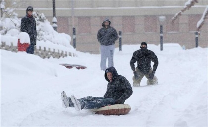 University of Nevada Reno student David Tidwell slides down a hill on the UNR campus as his friends watch on Monday, Dec. 7, 2009. Over a foot of snow has fallen from the storm that started early Monday morning. All public schools and the university were closed because of the weather. (AP Photo/Reno Gazette-Journal, Andy Barron)