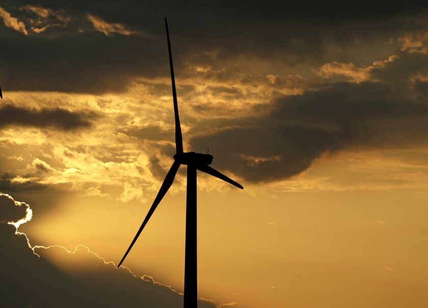 In this June 1, 2017 photo, a wind turbine, which is part of the Lost Creek Wind Farm, is silhouetted against the setting sun near King City, Mo. A new Associated Press-NORC Center for Public Affairs Research poll shows Americans are at least somewhat confident that the world will step up in its fight against global warming. But there are limits to their optimism. People also say their own actions can make a difference. (AP Photo/Charlie Riedel, File)
