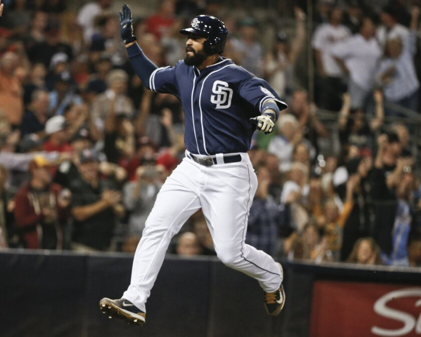 San Diego Padres' Matt Kemp sails through the air as he scores in the Padres' seven-run seventh inning against the St. Louis Cardinals in a baseball game Saturday, Aug. 22, 2015, in San Diego. (AP Photo/Lenny Ignelzi)
