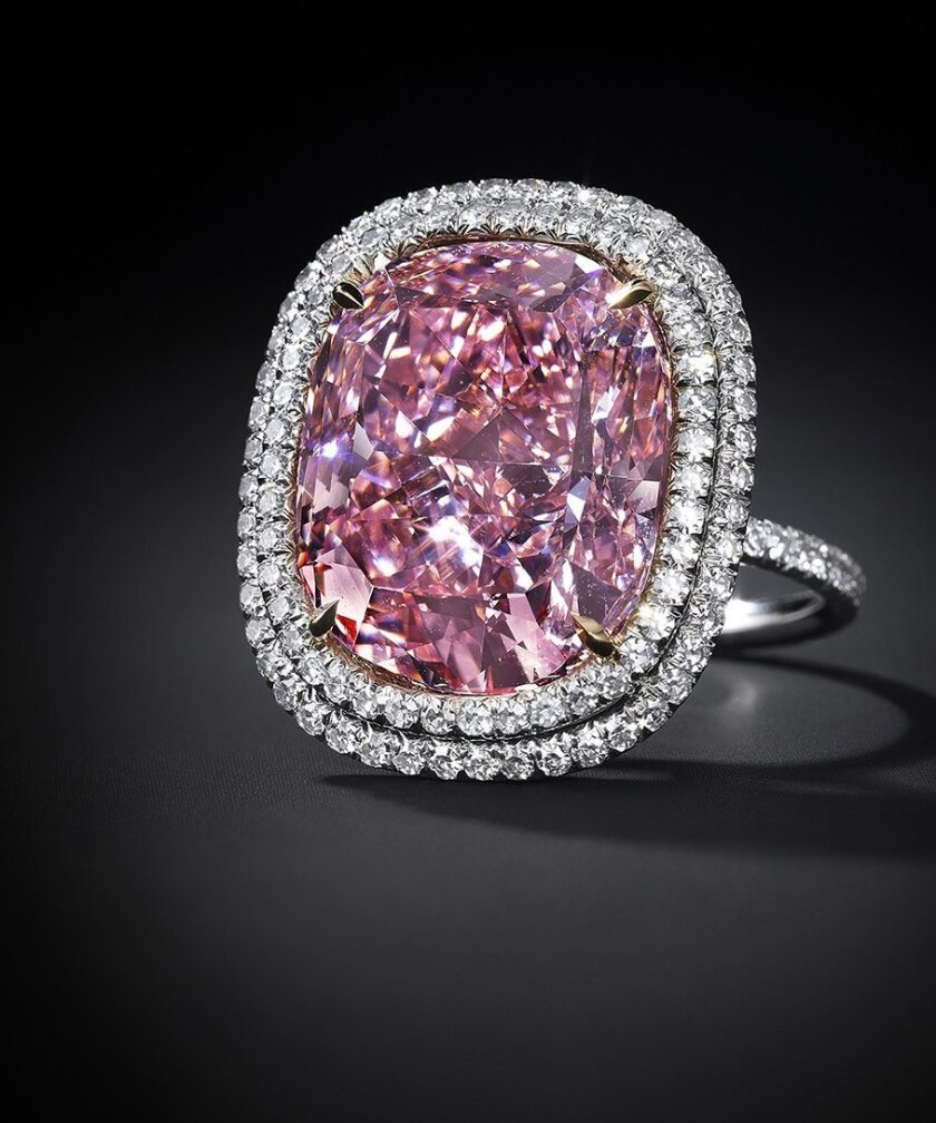 In this undated photo provided by Christie's Auction House in New York, a 16.08 carat, a pink diamond the size of a postage stamp is shown in a ring setting. It could set a record for a cushion-shaped fancy vivid pink diamond when it's offered Christie's at its Magnificent Jewels sale in Geneva on Nov. 10, where it is estimated to bring as much as $28 million. (Antfarm Photography/Christie's Auction House via AP)
