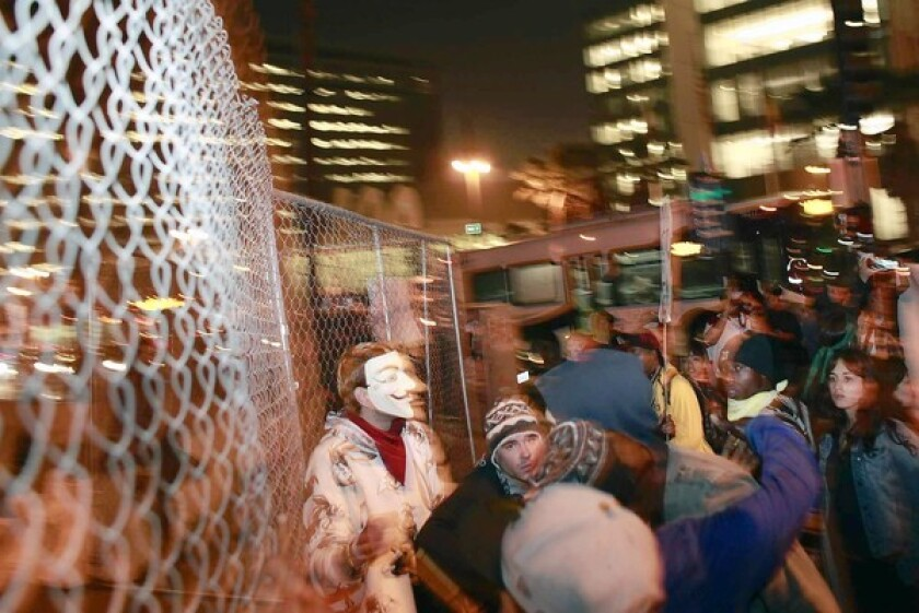 Occupy L.A. members gather near the fence erected around Los Angeles City Hall as they march along Spring Street toward the north steps of City Hall during a protest Wednesday night.