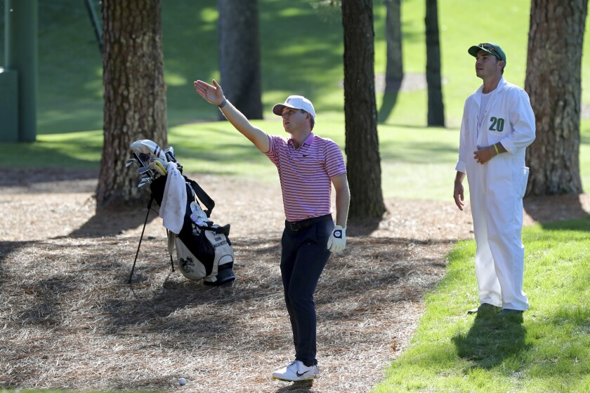 John Augenstein looks over his third shot with caddie William Kane on the 7th hole during the second round of the Masters Friday, Nov. 13, 2020, in Augusta, Ga. (Curtis Compton/Atlanta Journal-Constitution via AP)
