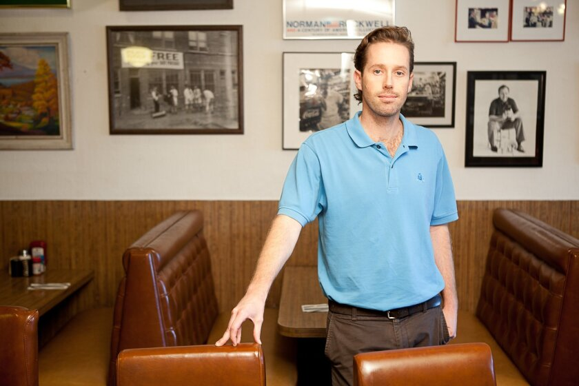 Owner John Rudolph stands in front of photos of both his father and grandfather, who operated a restaurant in New York.