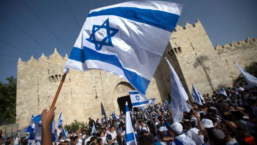 "Israelis hold national flags as they march at the Damascus Gate during the Jerusalem Day ""flag march"" in Jerusalem's Old City on June 5, 2016."