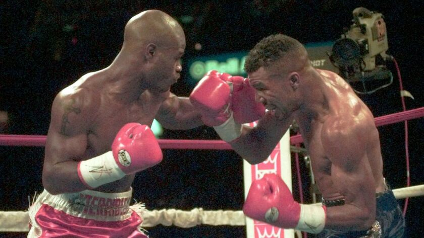 Terry Norris, left, of Campo, Calif., trades punches with Paul Vaden, of San Diego, during second-round action in IBF/WBC unification championship bout in Philadelphia Saturday night, Dec. 16, 1995.