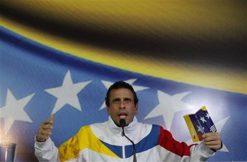 Opposition leader Henrique Capriles holds a copy of the constitution as he speaks during a press conference in Caracas, Venezuela, Monday, March 11, 2013. Capriles registered his candidacy to replace late President Hugo Chavez in elections scheduled for April 14th. (AP Photo/Ariana Cubillos)