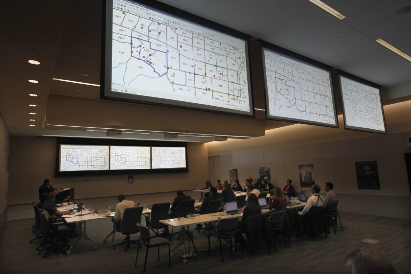 LAPD Assistant Chief Michel Moore leads a panel about crime trends as overhead maps display crime statistics by region, compiled with the department's CompStat system.