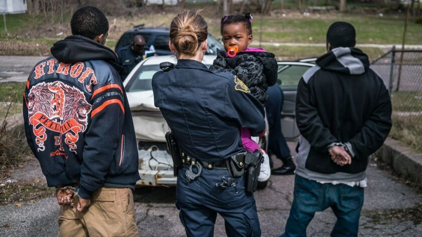 """Officer Bridgette Balasko holds a small child while her father is being searched and questioned in the Netflix documentary series """"Flint Town."""""""