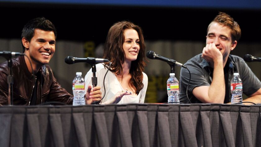 "Actors Taylor Lautner, left, Kristen Stewart and Robert Pattinson speak at ""The Twilight Saga: Break"