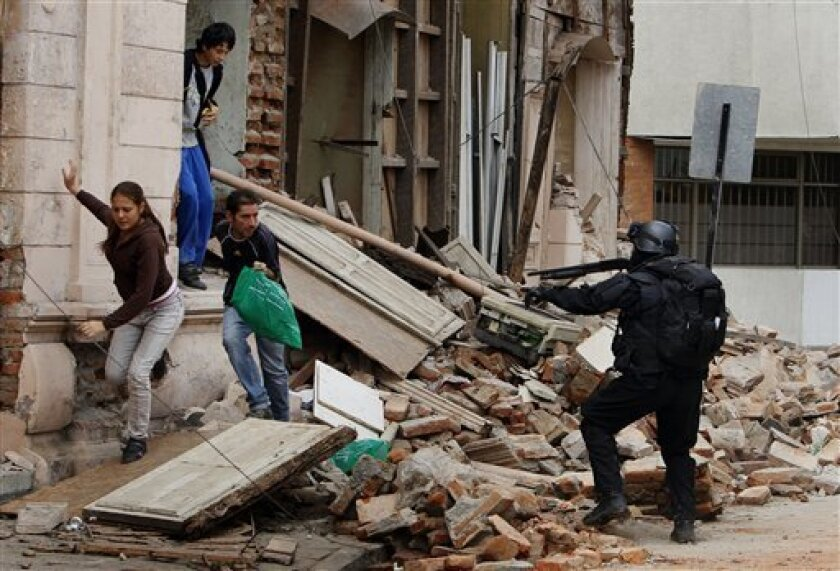 A police officer aims at people that were looting goods from a store damaged during the magnitude-8.8 earthquake in Talcahuano, Chile, Tuesday, March 2, 2010. (AP Photo/Ricardo Mazalan)
