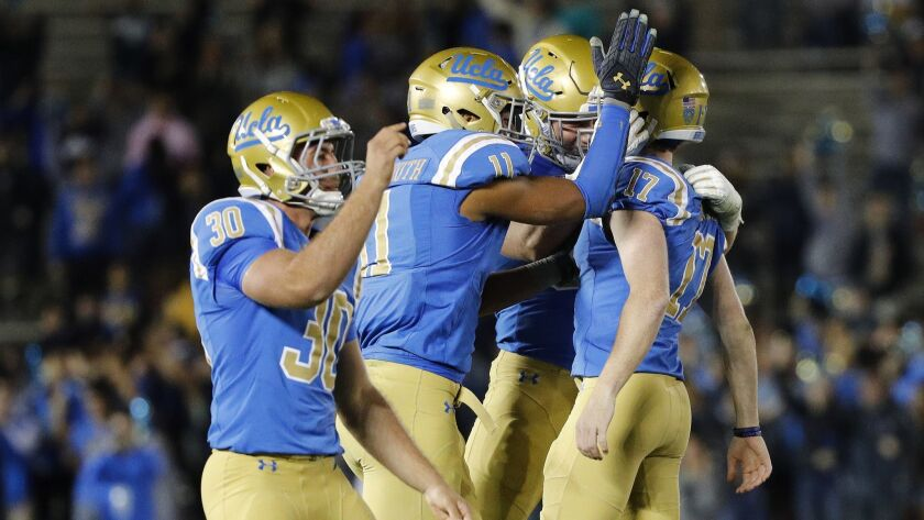 PASADENA, CA - NOVEMBER 24, 2017: Teammates swarm UCLA Bruins place kicker JJ Molson (17) after he