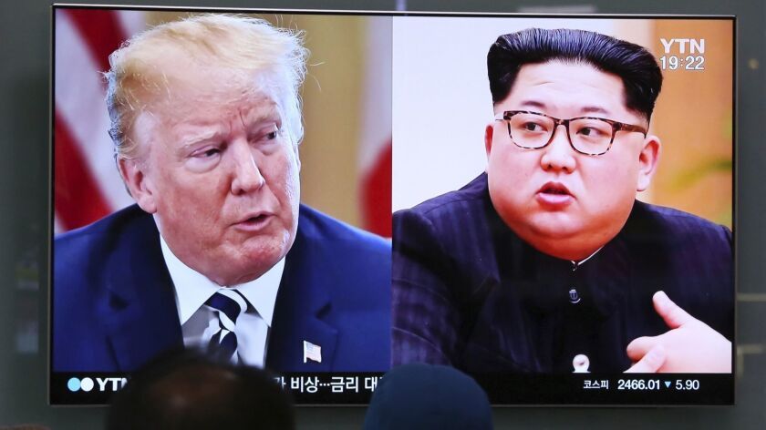 People watch a TV screen showing file footage of U.S. President Donald Trump, left, and North Korean leader Kim Jong Un in Seoul, South Korea.