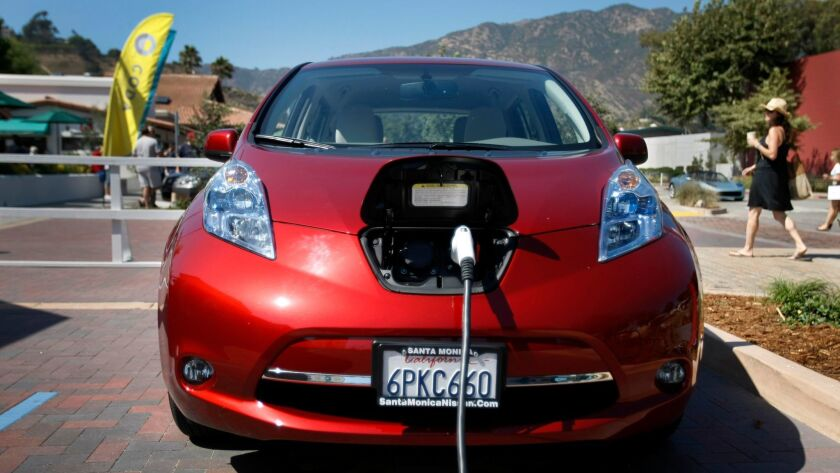 A Nissan Leaf is plugged into an electric-vehicle charging station at the Malibu Country Mart.