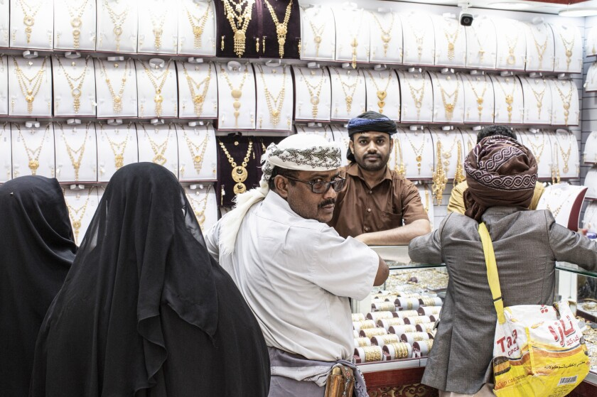 A family buys traditional Yemeni jewelry at a gold shop in the market area of Ataq in Shabwa Province, Yemen.