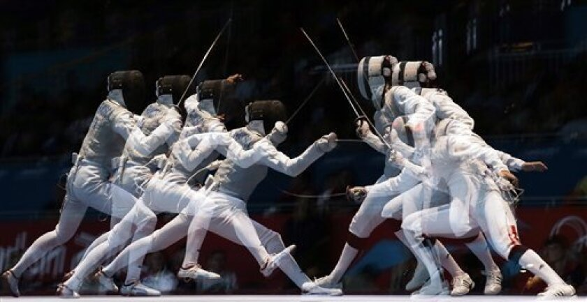 This multiple exposure photo shows France's Corinne Maitrejean and Italy's Elisa Di Francisca competing during a semifinals match at women's team foil fencing at the 2012 Summer Olympics, Thursday, Aug. 2, 2012, in London. (AP Photo/Pat Semansky)