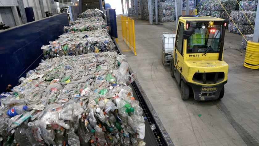 Used plastic bottles sit on a conveyor belt to be processed for recycling in Reidsville, N.C.