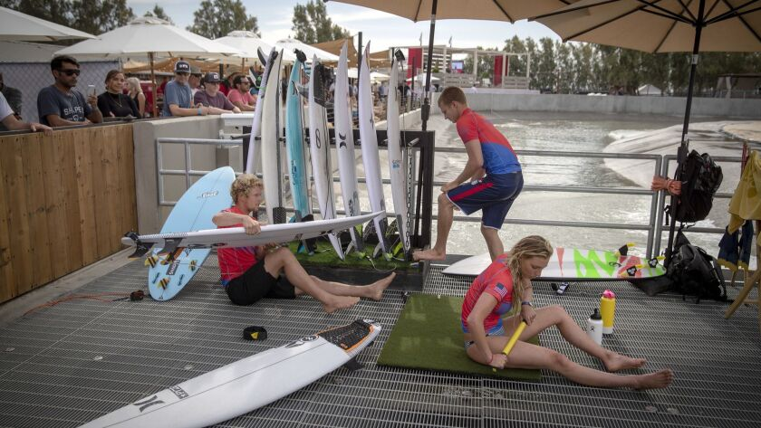Pro surfers representing U.S.A. team John John Florence, left, Kolohe Andino, center, and Lakey Peterson, of Montecito, warm up and stretch before surfing.