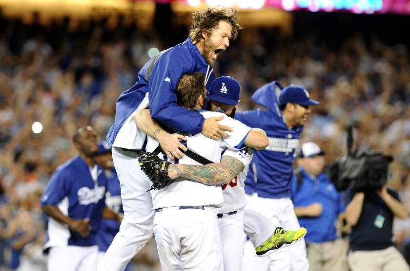 Winning pitcher Clayton Kershaw leaps onto catcher A.J. Ellis as the Dodgers celebrate their NL West title after defeating the San Francisco Giants, 9-1, on Wednesday night at Dodger Stadium.