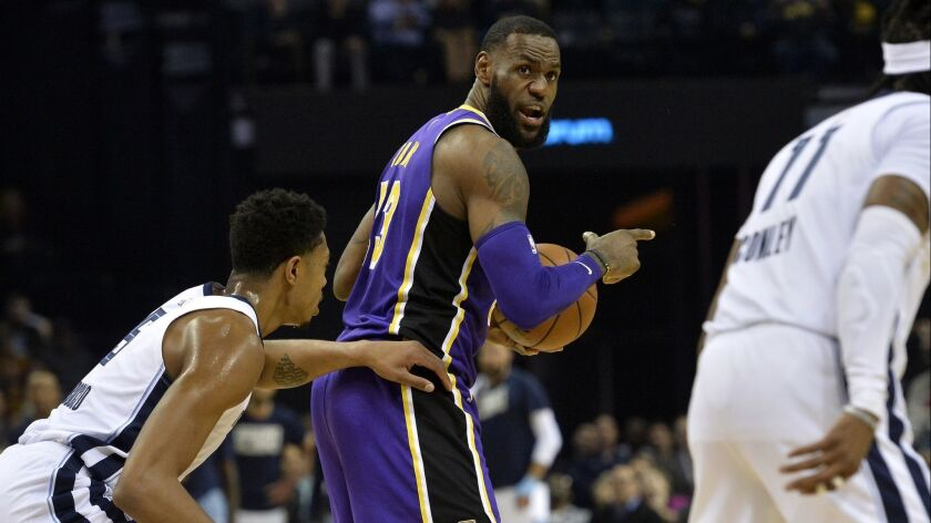 Los Angeles Lakers forward LeBron James, center calls to teammates as he controls the ball against M