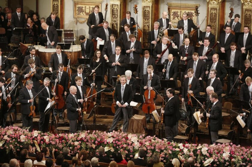 Conductor Franz Welser-Most and members of the Vienna Philharmonic Orchestra after its annual new year's concert in Vienna.