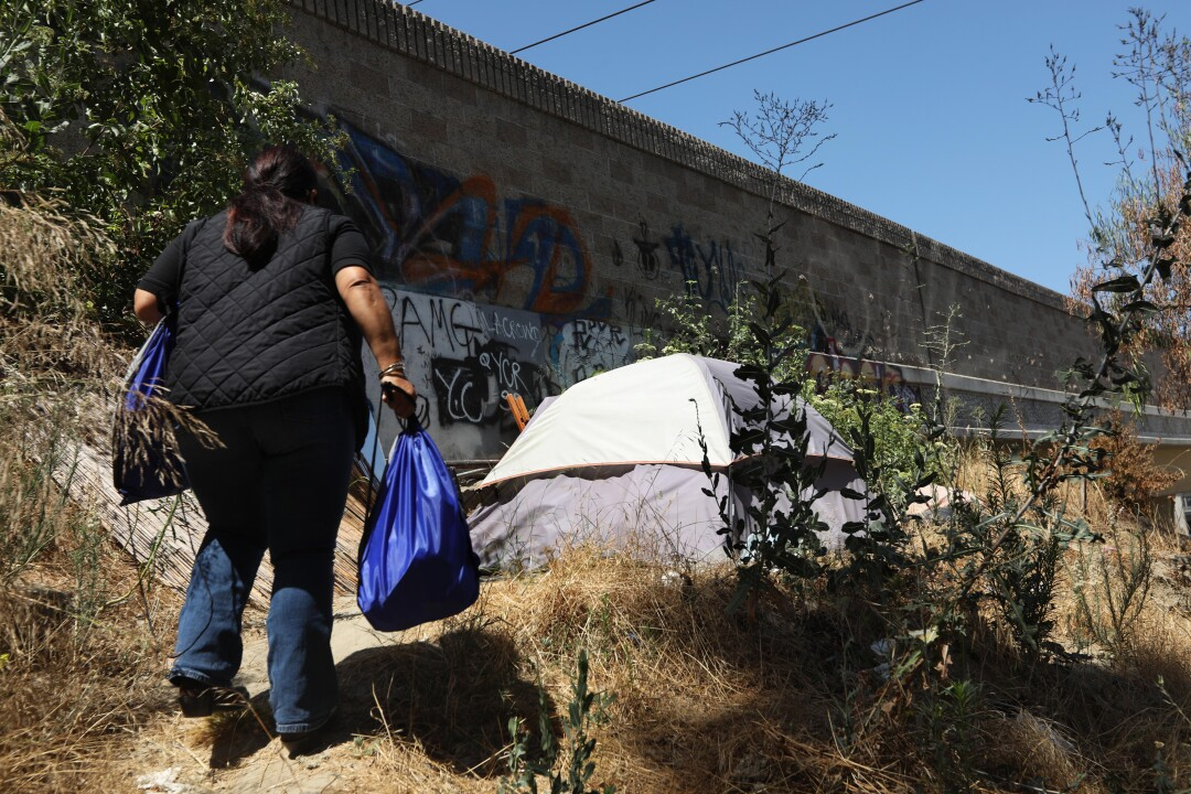 Outreach worker Kim Barnett takes food to a person along the 105 Freeway in Downey.