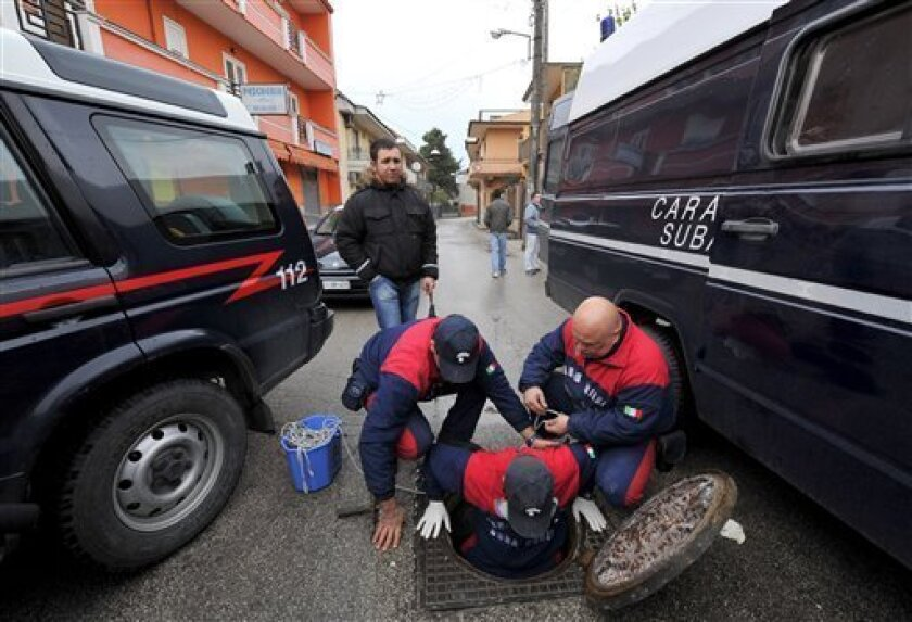 Italian Carabinieri paramilitary police officers inspect a manhole reportedly used by top mafia fugitive Giuseppe Setola to elude capture and escape from his hideout in Caserta, southern Italy, Monday Jan. 12, 2009. Carabinieri Col. Domenico Forte said police were closing in on Giuseppe Setola's hi