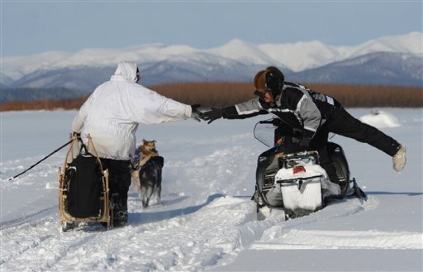 Four-time Iditarod champion Martin Buser reaches out to long-time friend and Nulato checker Larry Esmailka who drove down the Yukon River to help out with the race on Saturday, March 9, 2013. Buser was about 5 miles away from the Kaltag checkpoint and leading the sled dog race. (AP Photo/Anchorage Daily News, Bill Roth)