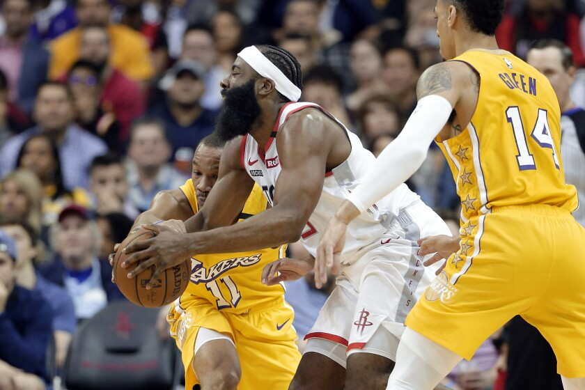 Rockets guard James Harden, center, tries to split the defense of Lakers guards Avery Bradley, left, and Danny Green during the first half of a game Jan. 18, 2020, in Houston.