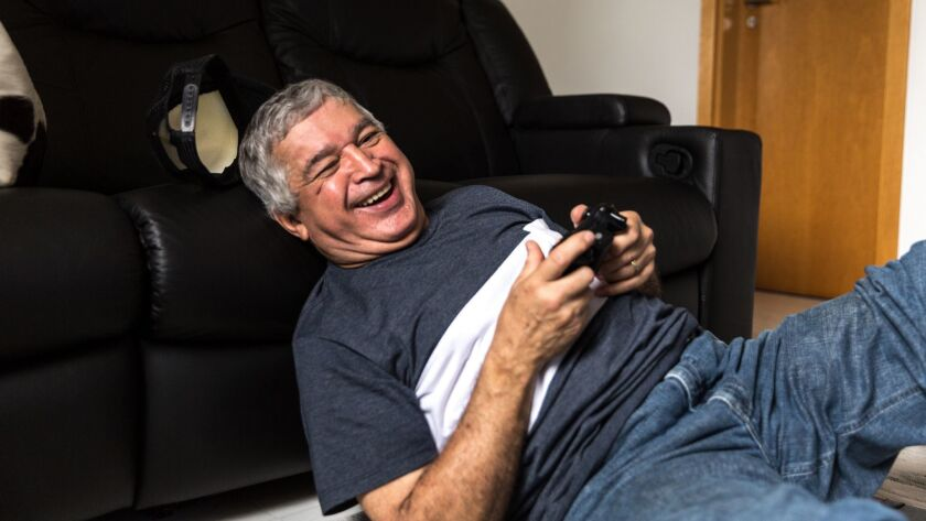 Active senior playing video games on console at home