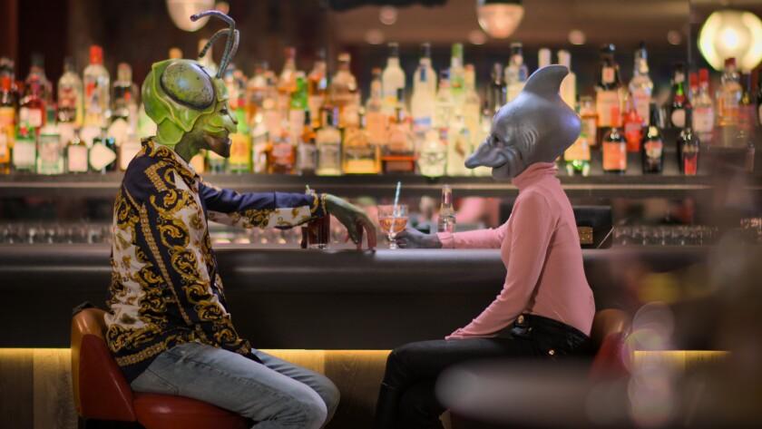 A couple in elaborate masks at a bar