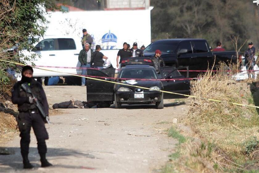 Policías ministeriales resguardan la zona donde fueron asesinados cinco policías en una emboscada. EFE/Archivo