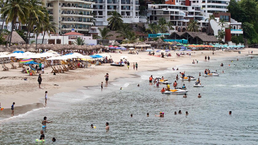 Sunbathers enjoy the beach at Puerto Vallarta, Mexico. A Southwest fare from Orange County to the Pacific Coast resort is available for $329.