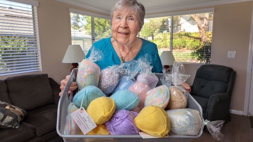 "Pat Anderson holds a basket full of her various ""Busters"" wardrobe accessories for breast cancer survivors."