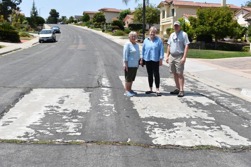 Residents Elaine Davis, Karen Meyer and Dave Meyer standing among some street problems on Azucar Way in Rancho Bernardo.
