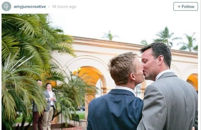 Two men kissing at a wedding in Balboa Park