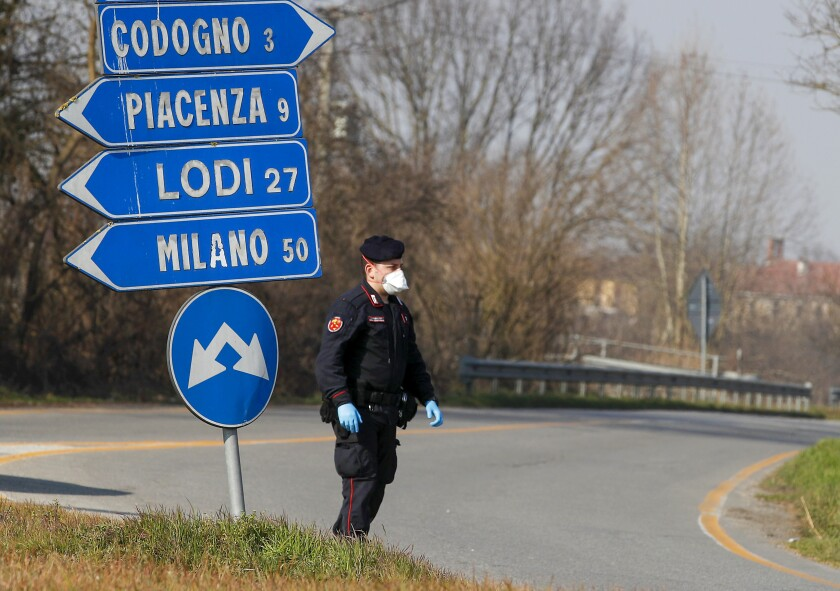 An Italian officer helps monitor traffic southeast of Milan, where the coronavirus has infected hundreds. A doctor traveling from Italy to the Canary Islands tested positive for the virus.