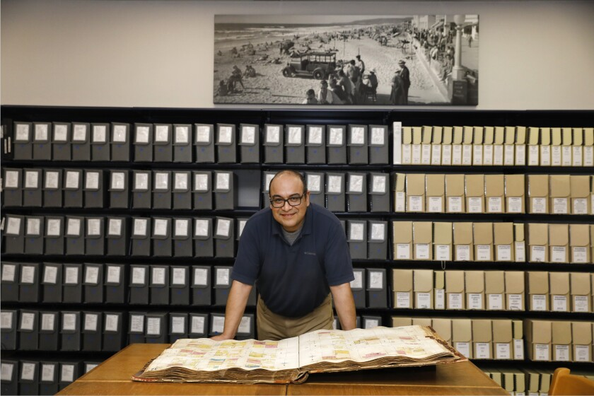 In this file photo from November of 2019, archivist Renato Rodriguez is shown inside the San Diego History Center's archives. While it is closed due to the coronavirus, the History Center is asking San Diegans to share their COVID-19 stories. These oral histories will become part of the center's collection.