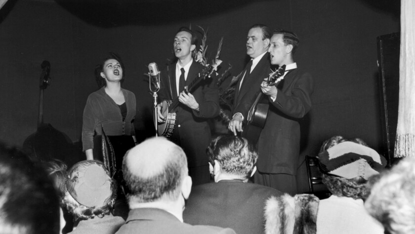 """The Weavers, Ronnie Gilbert, left, Pete Seeger, Lee Hays and Fred Hellerman perform at the Blue Angel nightclub in New York circa 1948. The group was known for spirited renditions of folk standards like Woody Guthrie's """"This Land Is Your Land,"""" """"Kumbaya"""" and """"On Top of Old Smokey."""" They belted out old union rallying cries and antiwar protest songs."""