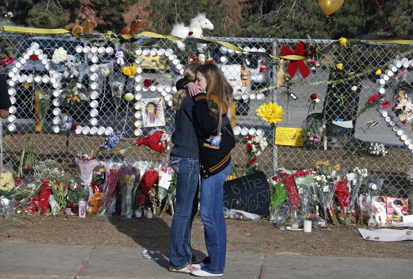 Arapahoe High School students hug at a tribute site honoring senior Claire Davis, who was hospitalized after being shot in the head by a fellow student Dec. 13. Davis died Saturday afternoon.