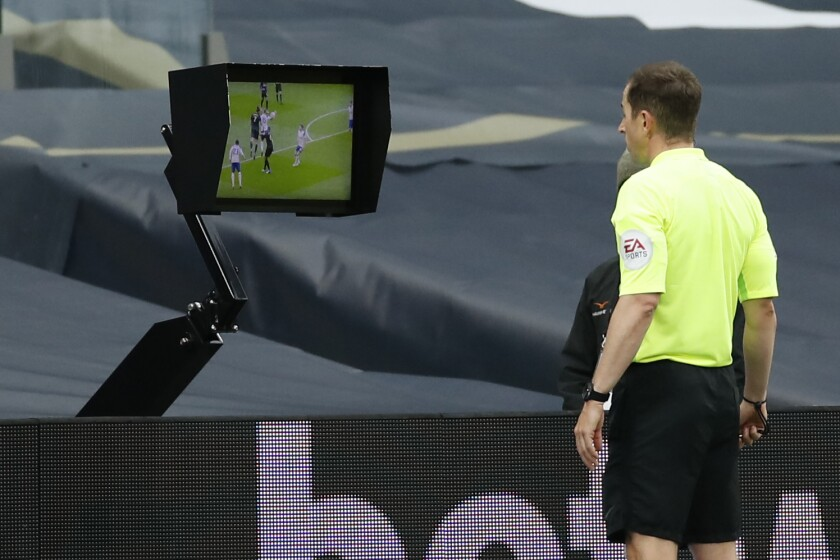 Referee Peter Bankes watches a monitor during the English Premier League soccer match between Tottenham and Newcastle at the Tottenham Hotspur Stadium in London, Sunday, Sept. 27, 2020. (Andrew Boyers/Pool via AP)