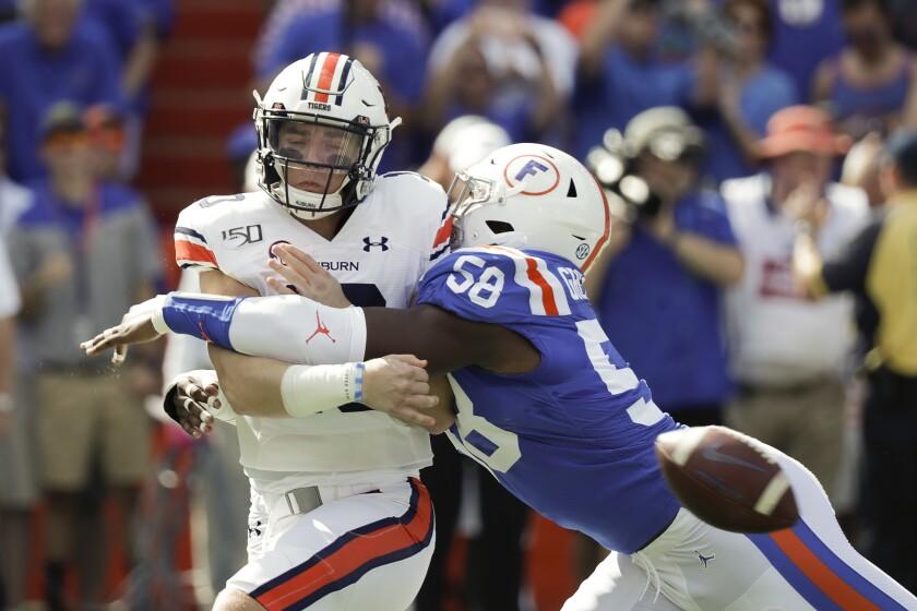 Auburn quarterback Bo Nix is hit by Florida linebacker Jonathan Greenard as he tries to pass during the first half Saturday.