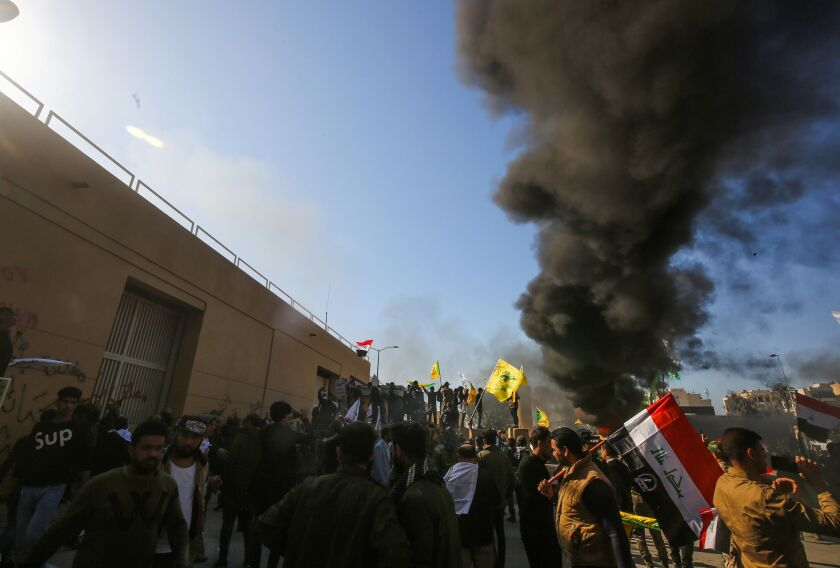 Iraqi protesters burn tires in front of the U.S. Embassy in Baghdad.