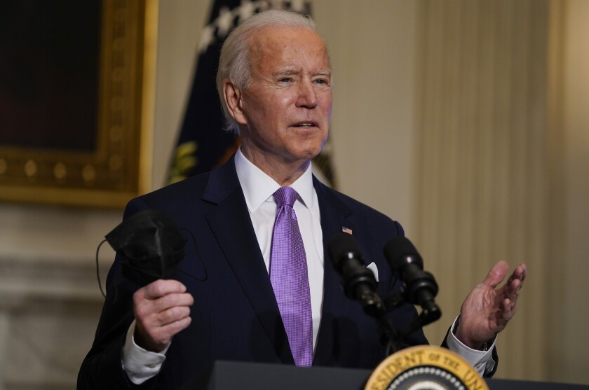 President Biden holds his face mask as he delivers remarks at the White House on Tuesday.