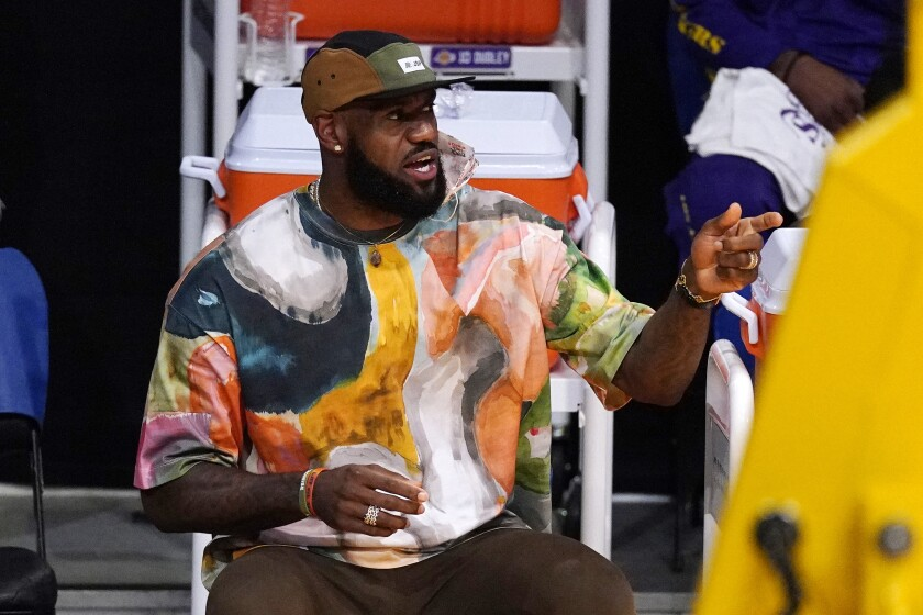 Los Angeles Lakers' LeBron James in street clothes watches from the bench.