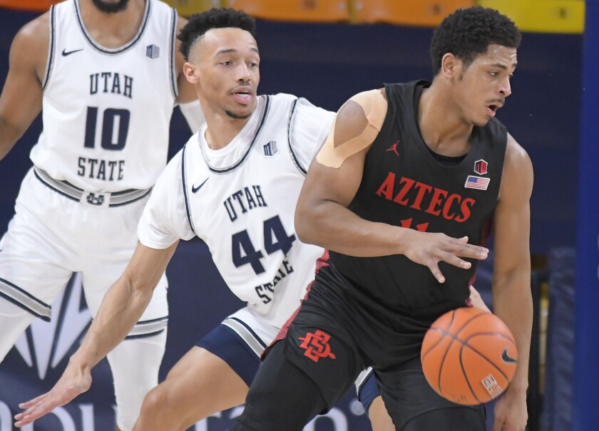 Matt Mitchell dribbles against Utah State's Marco Anthony before he was injured Thursday night.