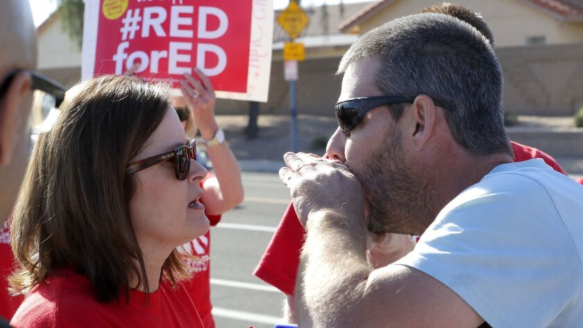 A parent of a Paseo Elementary student shouts at teacher Tammy Custis outside the school in Peoria, Ariz., on Wednesday.